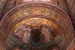 Исус Христос седнал върху син глобус на върха на купола, облечен в лилава дреха, и подаващ мъченическата корона на Свети Виталий с дясната си ръка в базиликата Сан Витале.