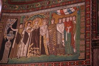 Императрица Теодора – тържествена и официална, със златен ореол, корона от скъпоценни камъни и свита от придворни дами в базиликата Сан Витале.