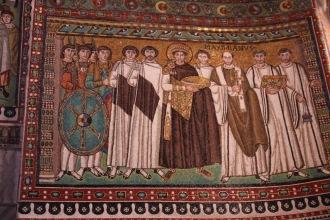 Император Юстиниан I, носещ златен ореол, стоящ до придворните си и епископ Максимилиан с преториански гвардейци и дякони в базиликата Сан Витале.