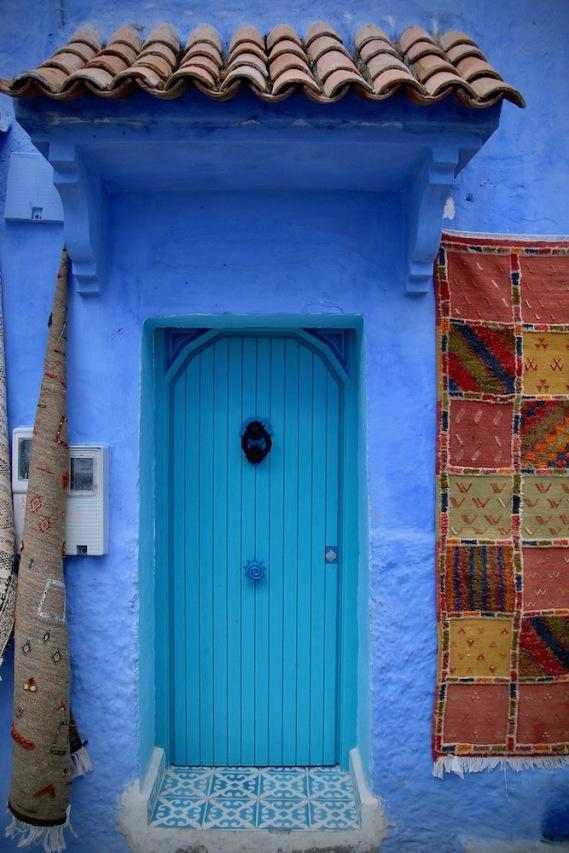 Малка спретната врата с два килима отпред.