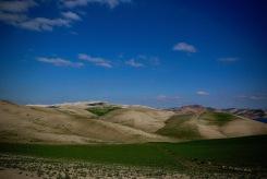 Обработваеми земи на фона на ниски планини.