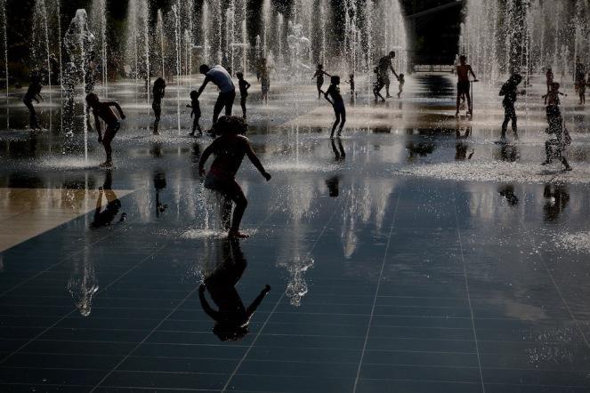 Забавляващите се деца са като скулптури на фона на фонтаните.