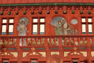 Фреските върху червената фасада на кметството.