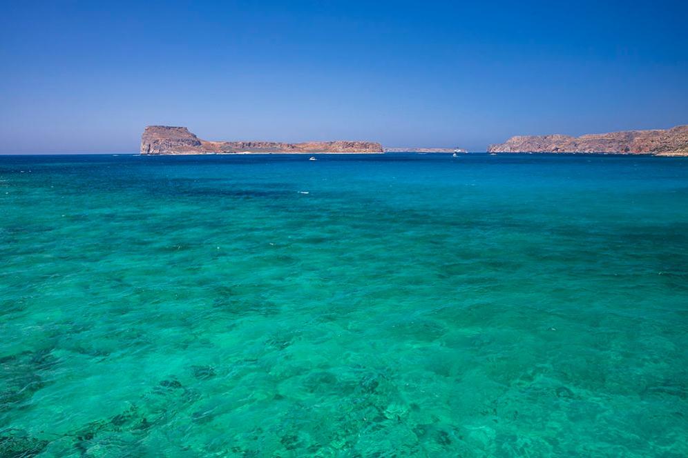 Цветът на водата преминава от смарагдово зелено в тюркоаз и достига до тъмно синьо в далечината.