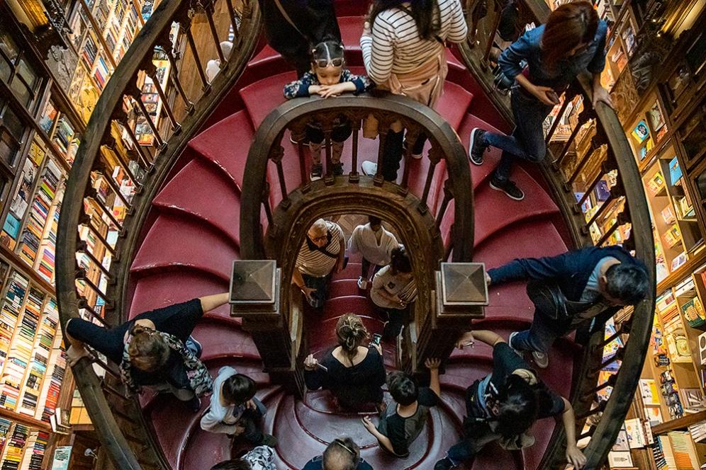 Извито, червено стълбище в книжарница Лело е завладяно от туристите.